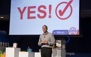 "A man speaks on stage. A presentation slide reads ""YES!"" on the wall behind him."