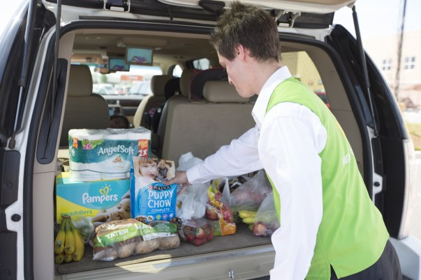 A male associate loads groceries into the trunk of a vehicle for grocery pickup