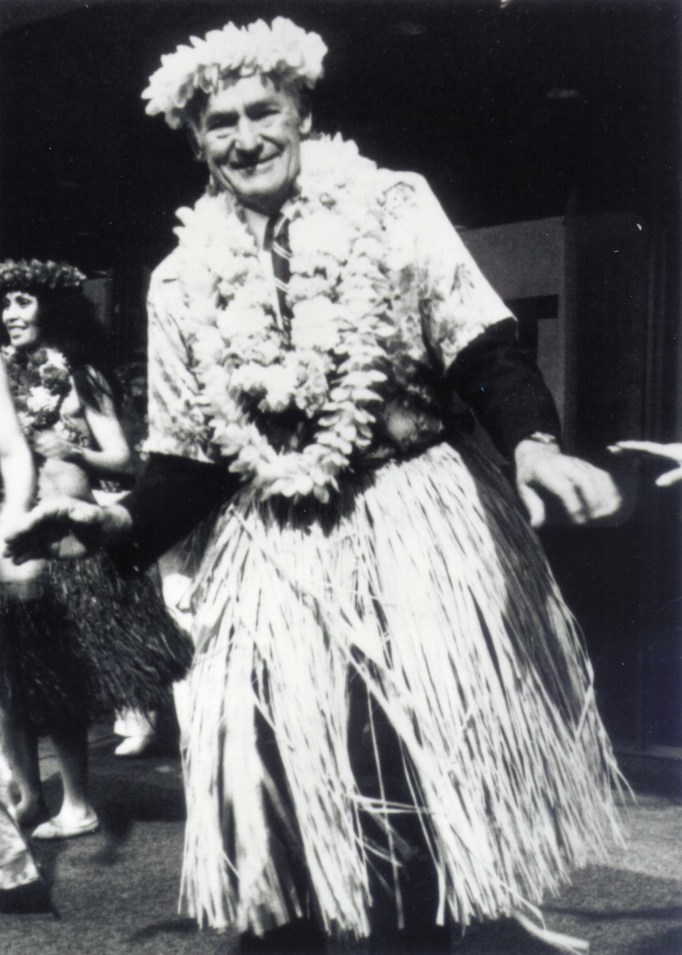 A black and white image of Sam Walton dressed in Hawaiian garb performs the hula on Wall Street
