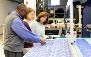 Three employees gather and review screen printed fabric at the LaRio Textile Manufacturing Lab