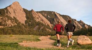 A male and a female are running with compression socks on a path by the foothills of low mountains