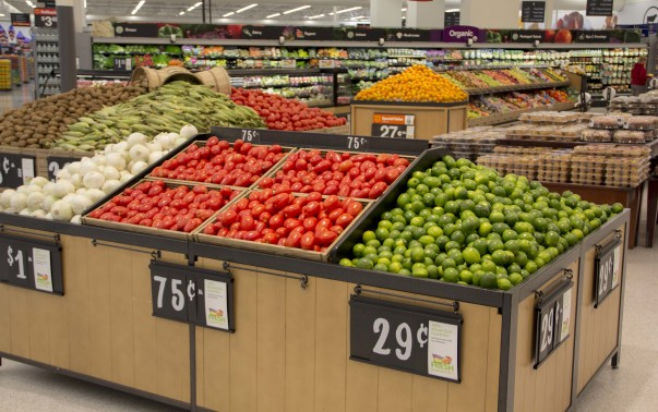 Bright red tomatoes and green limes are nicely organized in Walmart's produce department