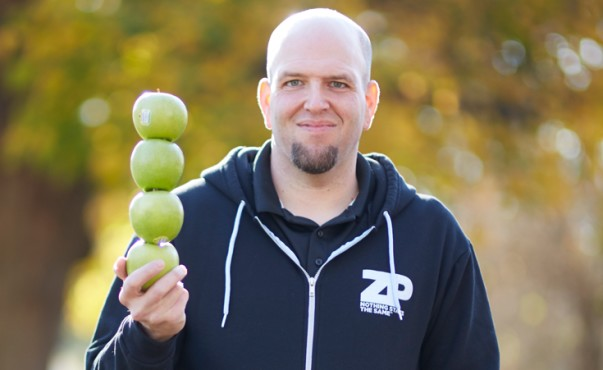 Man in black sweater holds skewer of green apples