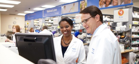 Two associates stand together at a desk in a Walmart pharmacy