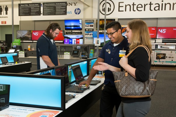 An associate and customer look at laptops in electronic department