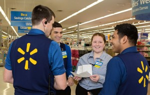 Four smiling Walmart associates in their navy vests gather in a circle