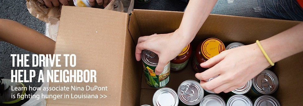 Cans and pasta sauce are being placed neatly in a cardboard box. Text overlay reads: THE DRIVE TO HELP A NEIGHBOR. Learn how associate Nina DuPont is fighting hunger in Louisiana >>