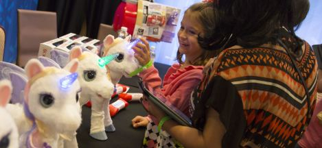 A young girl plays with a white unicorn that has a blue and green glowing horn