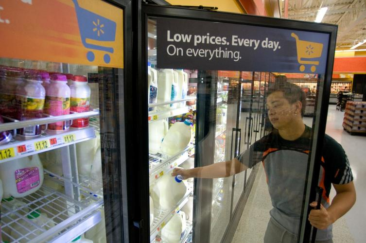 Walmart customer selects milk from a display case