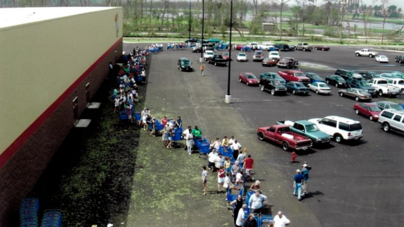 A long line of customers with blue shopping carts snake through a Sam's Club parking lot