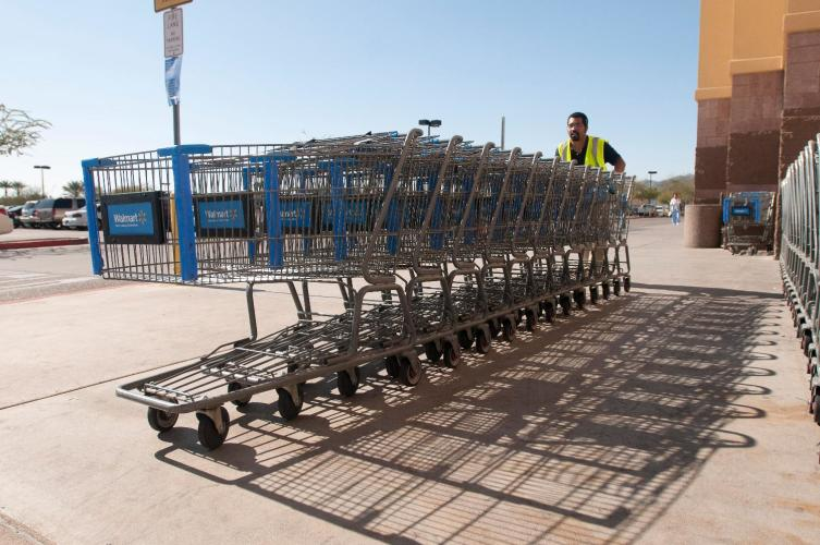 A Walmart associate pushes shopping carts at a Supercenter