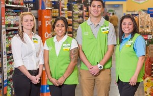 Four Walmart associates gather in a line in green vests in a Neighborhood Market