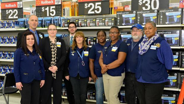 7 Associates in uniform standing in front of water filter display
