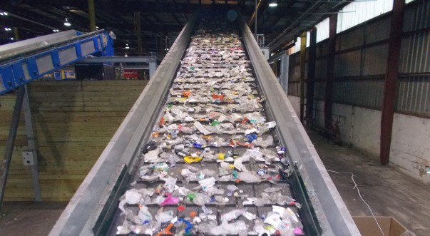 Plastic bottles move down a conveyor belt in a recycling facility