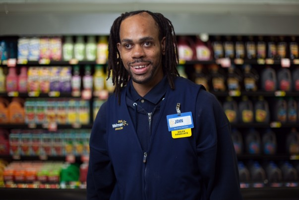 John Geeter is wearing a Walmart navy vest and is smiling in front of the dairy department