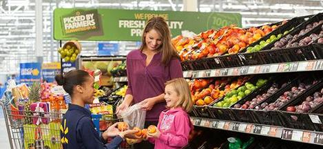 Associate Handing Apples to Smiling Child