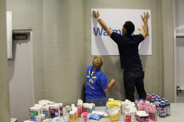Associate hanging a Walmart sign during Hurricane Harvey relief