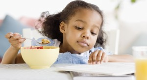 Young girl eating breakfast and reading at a table