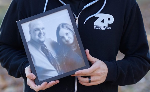 hands holds a picture of a man and his wife