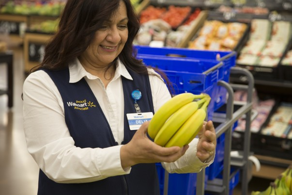 A female associate gets bananas ready for grocery pickup