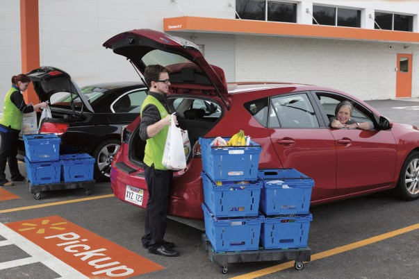 A male associate loading groceries in the pickup canopy