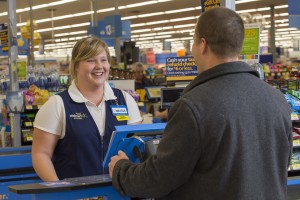 Walmart cashier Melissa is wearing her navy Walmart vest and smiles while helping a male customer at a register