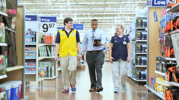 Three people walking together in a Walmart aisle