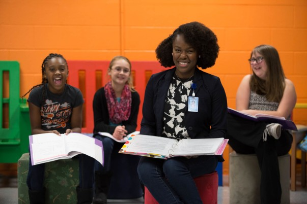 Associate Rianne Dixon sitting with young girls she mentors