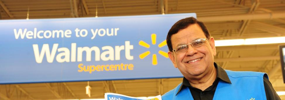 "Walmart Canada greeter associate poses by a ""Welcome to your Walmart Supercentre"" sign"