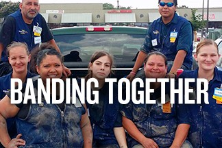 Mud-covered associates sit together smiling in the back of a truck. Text Reads: Banding Together