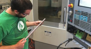 A man wearing a green shirt and safety glasses inspects a camouflage bar in front of an industrial machine.
