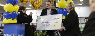 "Man with a cheque for $1000 stands beside two women clapping. Inflatable balloons spelling ""300"" are in the background."