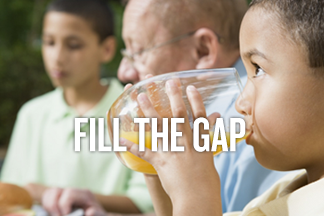 Text reads: Fill the gap. A young boy drinks orange juice from a glass.