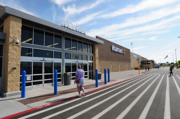 A customer walks towards a Walmart store entrance