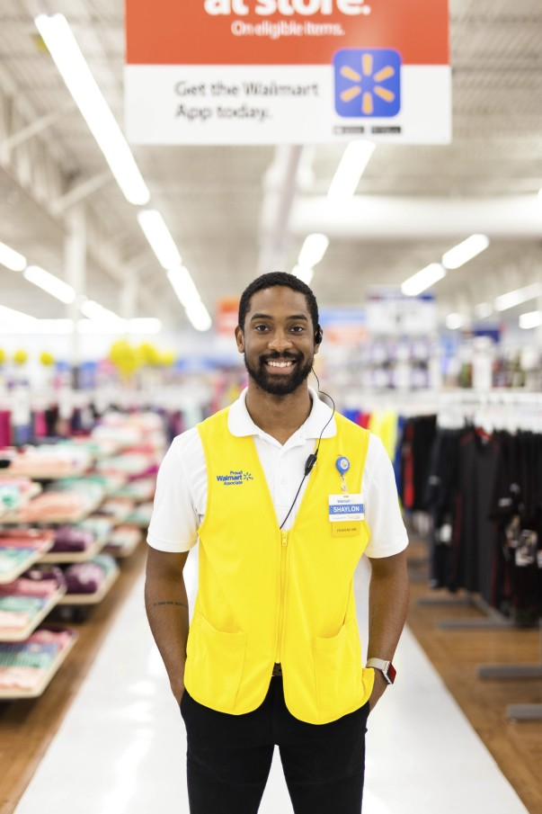 Male standing in a yellow vest standing in the aisle in Walmart