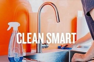 "A person wipes an industrial sink in an orange room with a blue sponge and sprayed cleaning product. Text overlay reads ""CLEAN SMART"""