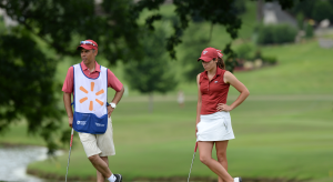 Gaby Lopez leans on her putter next to her caddie. Gaby is wearing Arkansas Razorbacks red and white while the caddie is wearing a white vest with a Walmart spark on the front.