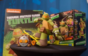 A toy Mikey from the Teenage Mutant Ninja Turtles is standing on a skateboard