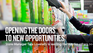 """Walmart associate Tara Lovelady smiles in a Walmart beauty aisle. Text reads: """"Opening the doors to new opportunities. Store manager Tara Lovelady is leading the way for others >>"""""""