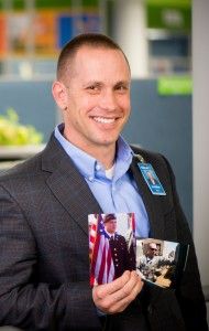 Jonathan Smith, veteran associate, holds military pictures of himself while in Walmart's corporate office