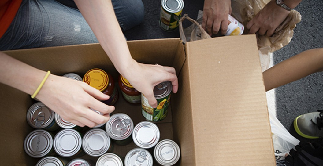 Close Up of Hands Loading a Box with Canned Goods