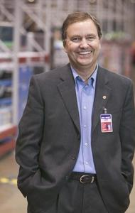 Lee Scott smiles with his hands in his pockets in a gray suit. His name badge hangs off the right side of his jacket.