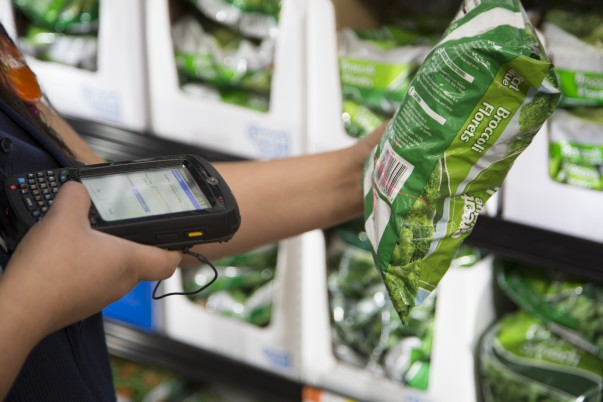 An associate scans vegetables for grocery pickup