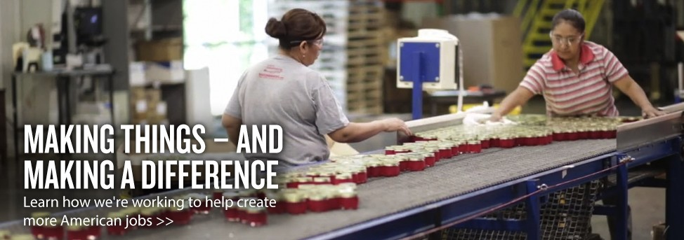 Two women are working near a conveyor belt in a candle factory. Text reads: Making things - and making a difference. Learn how we're working to help create more American jobs.