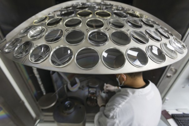 A piece of metal contains circular cutouts filled with glass lenses