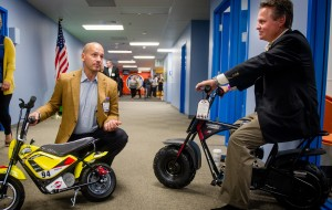 Two representatives from Monster Moto pitch two mini motorcycles in the hallways of Walmart's Home Office building