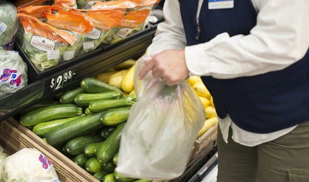A woman places cucumbers in a produce bag