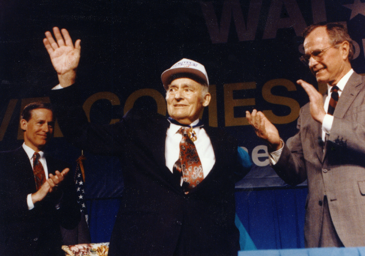 Sam Walton Receives Medal of Freedom. Sam waves to the crowd while others clap in the background.