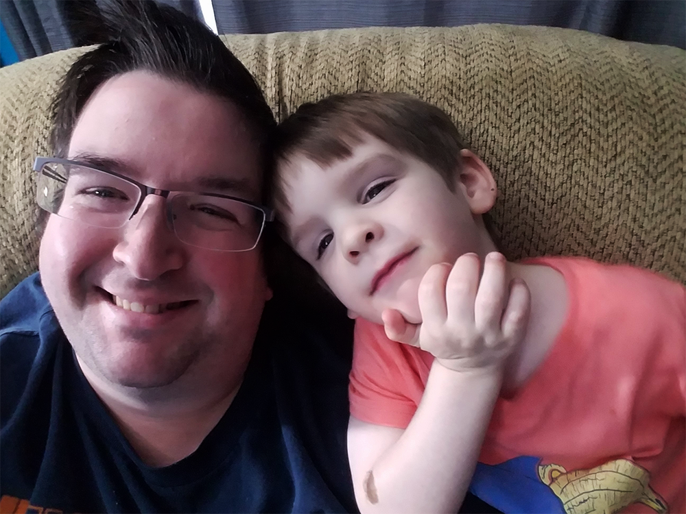 Associate Dustin sitting on couch with son