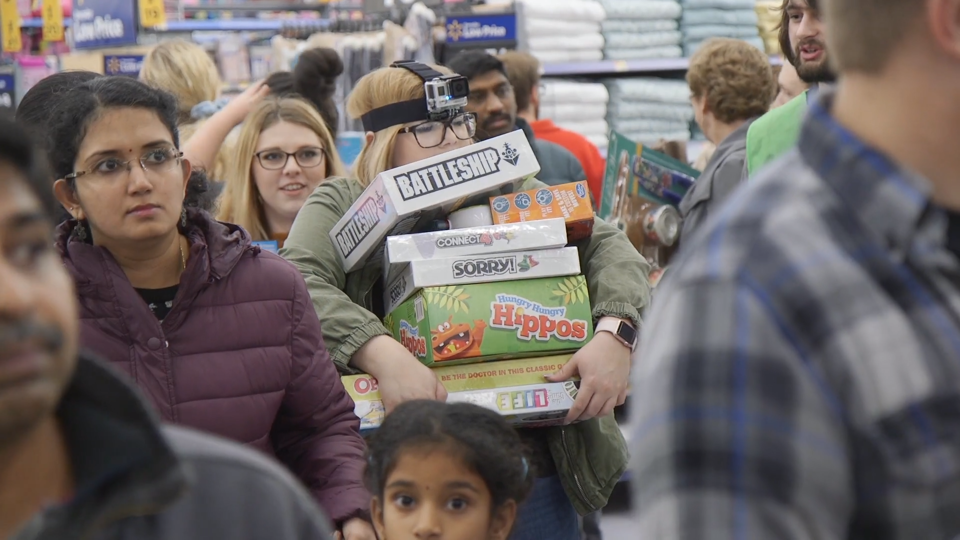 A customer carries a stack of board games during Black Friday 2018